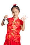 Asiatisk flicka i reko tecken för kinesisk cheongsamklänningshow med en klocka Fotografering för Bildbyråer
