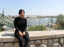 Asiatisk flicka, kvinna som poserar i den Budapest, frihetbron och Donau Arkivfoton