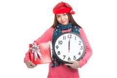 Asiatisk flicka med den röda asken och klockan för julhattgåva Arkivfoton