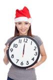 Asiatisk flicka med den röda den santa hatten och klockan Arkivfoto