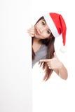 Asiatisk flicka med den santa hatten som bakifrån kikar en tom teckenpunkt Arkivfoton