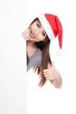 Asiatisk flicka med den santa hatten som bakifrån kikar en tom teckenshow Royaltyfri Bild