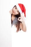 Asiatisk flicka med den santa hatten som bakifrån kikar en tom teckenshow Arkivfoton