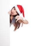 Asiatisk flicka med den santa hatten som bakifrån kikar en tom teckenshow Royaltyfria Bilder
