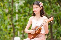 Asiatisk flicka med den utomhus- ukulelegitarren Royaltyfri Foto