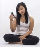 Asiatisk flicka med en smart telefon arkivfoto