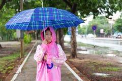 Asiatisk flicka med paraplyet och regnrocken fotografering för bildbyråer