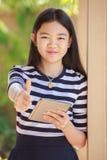 Asiatisk flicka- och datorminnestavla i handanseende med toothy smil Fotografering för Bildbyråer