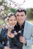 Asiatisk flicka- och europégrabb som poserar bland av att blomstra mandelbr Arkivbilder