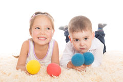 Asiatisk flicka och europépojke som spelar med bollar Arkivfoto