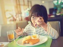 Asiatisk flicka som äter frukosten med pyjamas Arkivfoton