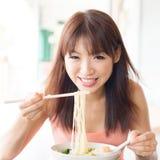 Asiatisk flicka som äter ramen Arkivbild