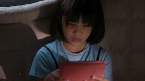 Asiatisk flicka som använder minnestavladatoren i mörkret som är ensamt arkivfilmer