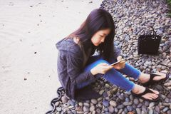 Asiatisk flicka som använder smartphonen Royaltyfria Bilder