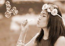 Asiatisk flicka som blåser såpbubblor, utomhus- stående Royaltyfri Bild
