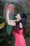 Asiatisk flicka som dricker från lerakrukan Royaltyfri Bild