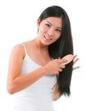 Asiatisk flicka som kammar hår Royaltyfria Bilder