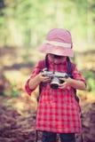 Asiatisk flicka som kontrollerar foto i digital kamera abstrakt bildtappning för bakgrund 3d Arkivfoto