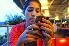 Asiatisk flicka som kontrollerar telefonen i en restaurang Arkivfoto