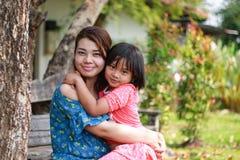 Asiatisk flicka som kramar hennes moder Arkivfoto