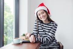Asiatisk flicka som ler sammanträde i coffee shop, kvinna som bär Santa Cl arkivbilder