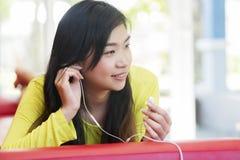 Asiatisk flicka som ligger på soffan och lyssnar till musik royaltyfri fotografi