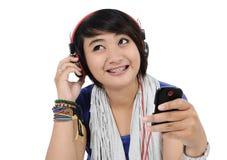 Asiatisk flicka som lyssnar till sånger Arkivfoton