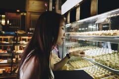 Asiatisk flicka som pekar på kinesiska bakelser Royaltyfria Bilder