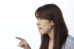asiatisk flicka som pekar till vänster fotografering för bildbyråer