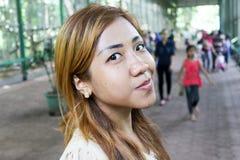 Asiatisk flicka som poserar på fullsatt med folkgatan Royaltyfri Fotografi