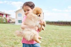 Asiatisk flicka som rymmer den älsklings- hunden Royaltyfria Foton