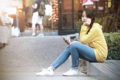 Asiatisk flicka som rymmer en smartphone på ett ställe i Chiang Mai, Thailand arkivfoton