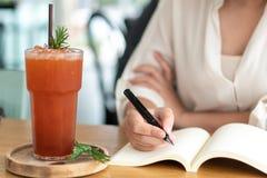 Asiatisk flicka som rymmer en svart penna som skriver in i en tom bok Dagbokhandstilber?ttelser antecknade m?ktigt Minnen p? en t royaltyfri bild