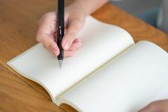 Asiatisk flicka som rymmer en svart penna som skriver in i en tom bok Dagbokhandstilber?ttelser antecknade m?ktigt Minnen p? en t arkivbild