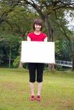 Asiatisk flicka som rymmer ett plakat utomhus- royaltyfria bilder