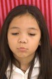 asiatisk flicka som ser den SAD ståenden Arkivbild