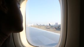 Asiatisk flicka som ser till och med fönstret flygplatsen från flygplanet lager videofilmer