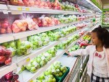 Asiatisk flicka som shoppar i supermarket som ser ny frukt på hylla royaltyfri foto