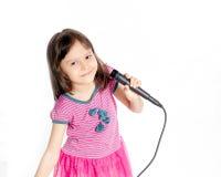 Asiatisk flicka som sjunger med mikrofonen Arkivfoto