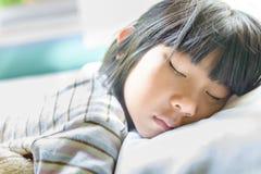 Asiatisk flicka som sover på säng som täckas med filten Fotografering för Bildbyråer