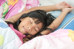 Asiatisk flicka som sover på säng som täckas med filten Arkivbild