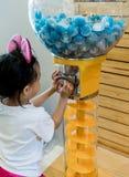 Asiatisk flicka som spelar lycklig attraktion från bollvaruautomaten Arkivfoto