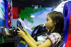 Asiatisk flicka som spelar maskinen för springa för bil den modiga på en av shoen arkivbild