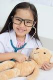 Asiatisk flicka som spelar som en doktor Arkivbild