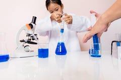 Asiatisk flicka som spelar som en forskare för att experimentera med laboratoriumutrustning royaltyfria bilder