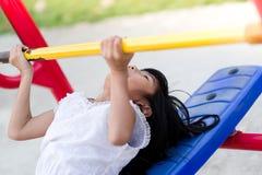 Asiatisk flicka som spelar utomhus- konditionutrustning Fotografering för Bildbyråer