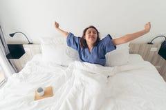 Asiatisk flicka som sträcker kroppen, når att ha vaknat upp i morgonen M royaltyfri fotografi