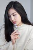 Asiatisk flicka som tänker och rymmer en penna royaltyfri fotografi