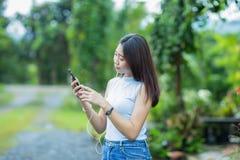 Asiatisk flicka som talar på telefonen i trädgården Royaltyfri Bild