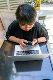 Asiatisk flicka som utanför använder smartphonen arkivfoto